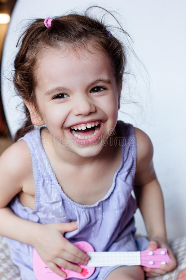获得愉快的小女孩使用与玩具吉他或尤克里里琴的乐趣 免版税图库摄影