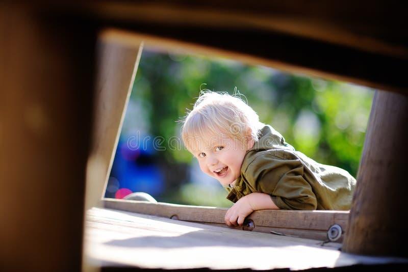 获得愉快的小男孩在室外操场的乐趣 免版税库存照片
