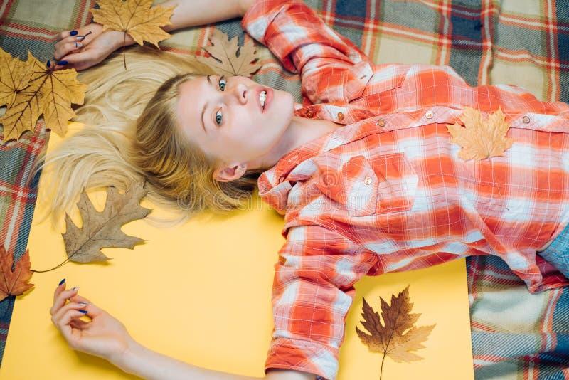获得愉快的年轻女人与叶子秋天的乐趣 使用与叶子的美丽的肉欲的金发碧眼的女人 时尚画象美丽 免版税库存照片