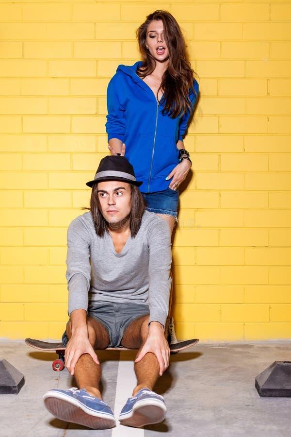 获得愉快的年轻的夫妇在黄色砖墙前面的乐趣 库存图片