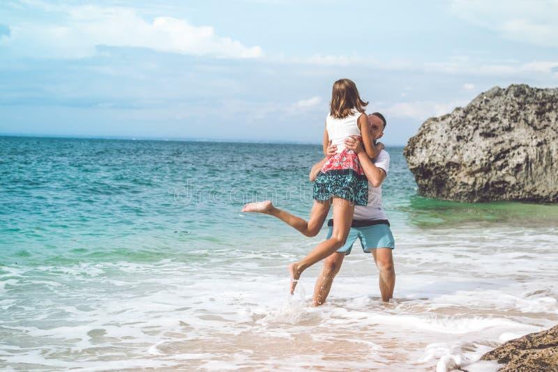 获得愉快的年轻蜜月的夫妇在海滩的乐趣 海洋,在巴厘岛的热带假期,印度尼西亚 免版税库存图片