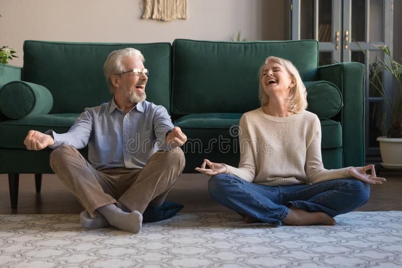获得愉快的成熟的夫妇乐趣,实践的瑜伽一起在家 免版税库存图片