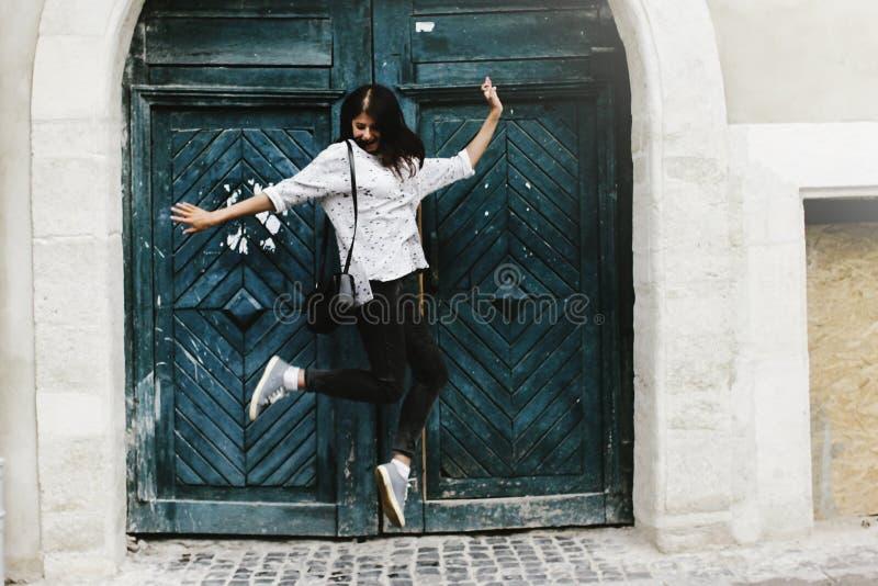 获得愉快的时髦的行家的妇女跳跃和乐趣 免版税图库摄影