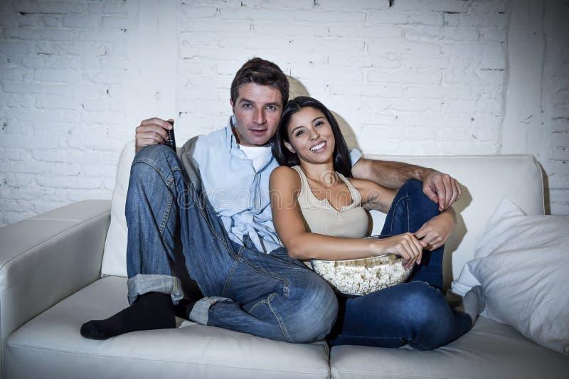获得愉快的有吸引力的夫妇享用的乐趣看电视在家放松了 免版税库存图片
