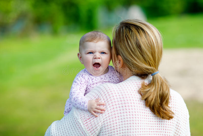 获得愉快的母亲与新出生的小女儿的乐趣户外 免版税库存照片