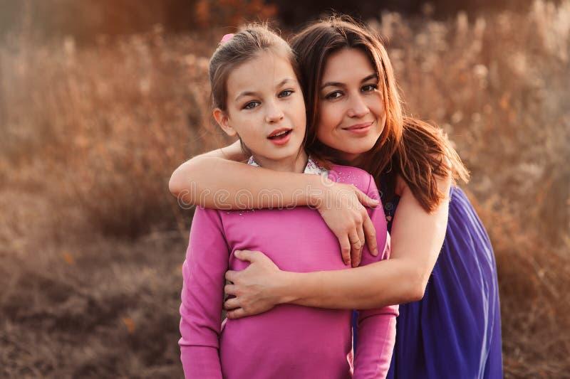 获得愉快的母亲和青春期前的女儿生活方式捕获室外的乐趣 一起花费时间的爱恋的家庭在步行上 免版税库存图片