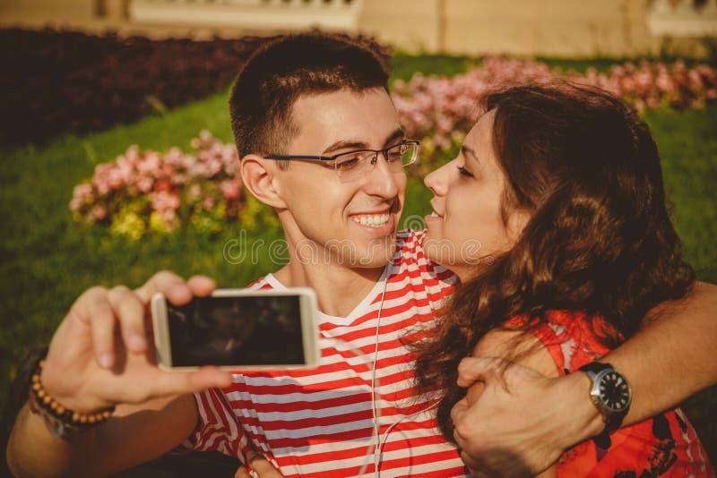 获得愉快的美好的夫妇采取在手机的selfie,一起拥抱和乐趣 免版税库存照片