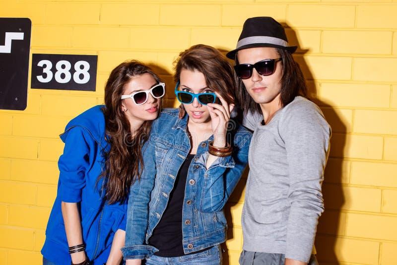 获得愉快的青年人在黄色砖墙前面的乐趣 库存照片