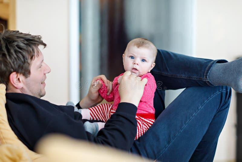 获得愉快的骄傲的年轻的父亲与新出生的小女儿,家庭画象的乐趣一起 有女婴的,爱爸爸 新 免版税库存照片