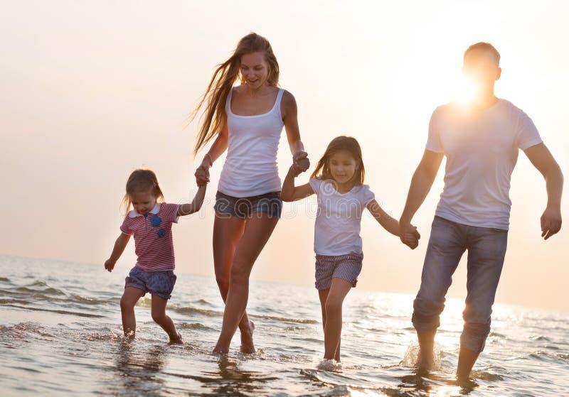 获得愉快的年轻的家庭跑在海滩的乐趣在日落 免版税库存图片