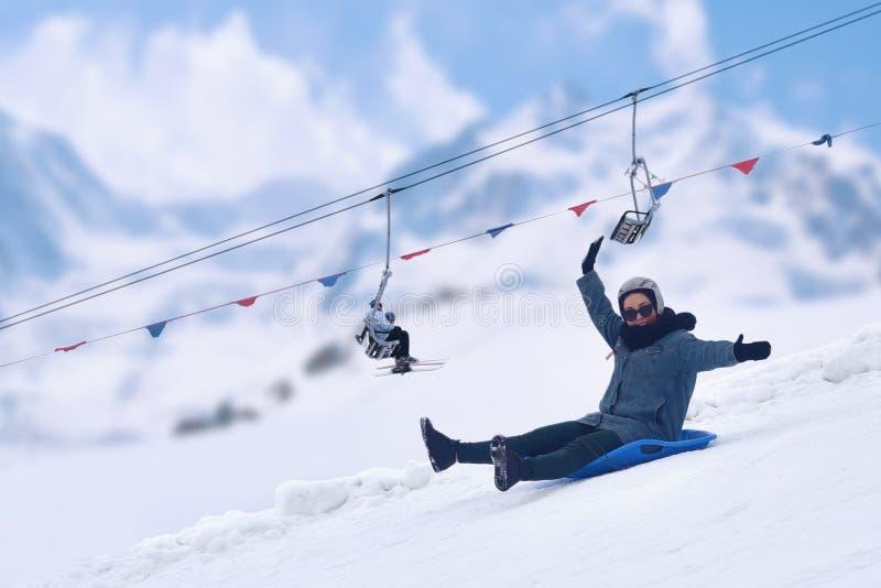 获得成人的女孩乐趣 在雪撬的风筝,笑,象孩子的微笑 美丽的概念礼服女孩纵向佩带的空白冬天 免版税图库摄影