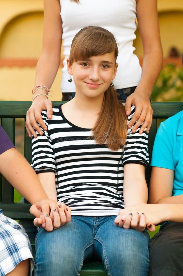 获得技术支持的逗人喜爱的愉快的十几岁的女孩从frien 库存照片