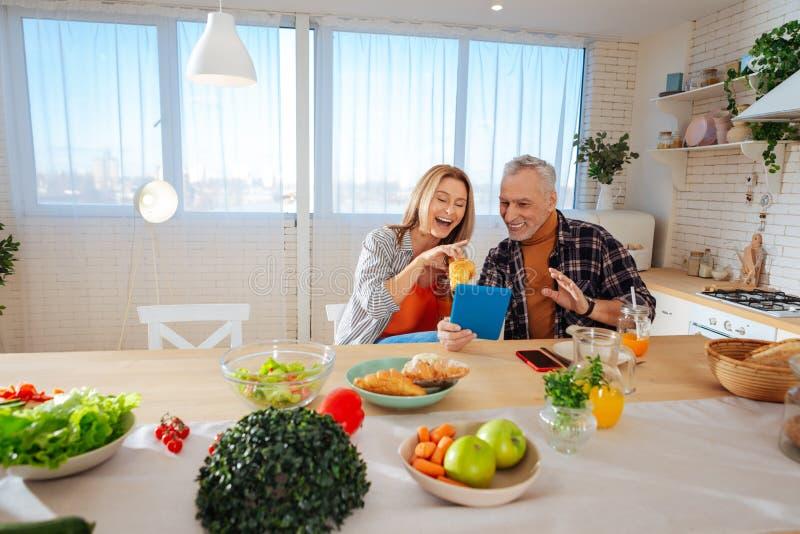 获得放光的夫妇乐趣,当享用早餐时 免版税图库摄影