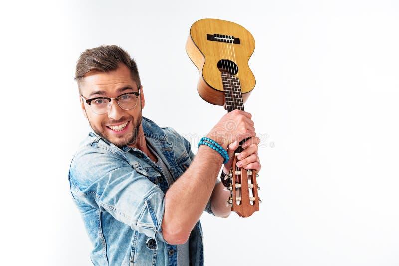 获得无忧无虑的人与吉他的乐趣 免版税库存照片