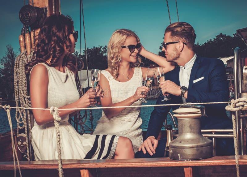 获得时髦的富裕的朋友在豪华游艇的乐趣 库存照片