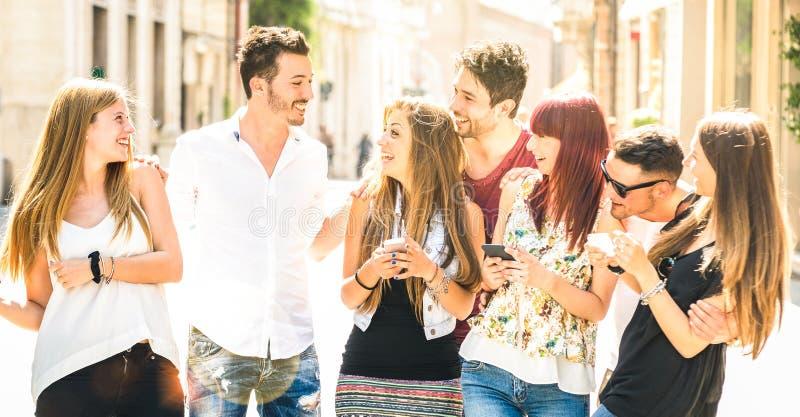 获得最好的朋友的小组一起走在城市街道-技术在每天生活方式的互作用概念上的乐趣与 免版税库存图片
