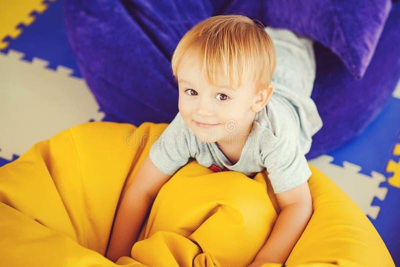 获得激动的孩子在辎重袋的乐趣在家 愉快的童年 逗人喜爱的笑的小男孩获得乐趣在现代孩子室 画象o 免版税库存图片