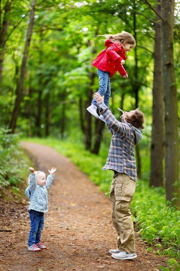 年轻获得父亲和他的两个的小孩乐趣 免版税图库摄影