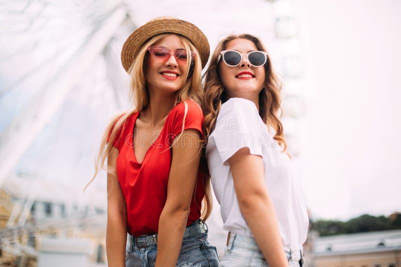 获得特写镜头画象愉快的微笑的俏丽的女孩乐趣 时髦地穿戴在短的牛仔布短裤和明亮的T恤杉,太阳镜 库存图片