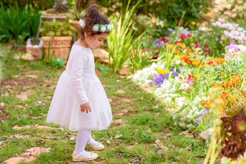 获得白色礼服和花的花圈的滑稽的女孩乐趣夏天庭院 免版税库存图片