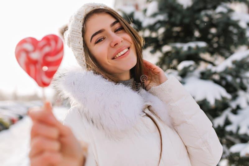 获得白色被编织的帽子的被启发的年轻女人与桃红色心脏棒棒糖的乐趣在街道上充分雪 有吸引力 库存照片