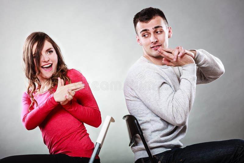 获得的夫妇乐趣假装手指是枪的手 免版税库存图片