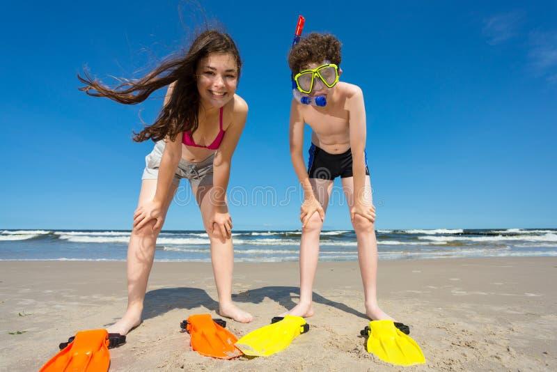 获得的女孩和的男孩在海滩的乐趣 免版税库存图片