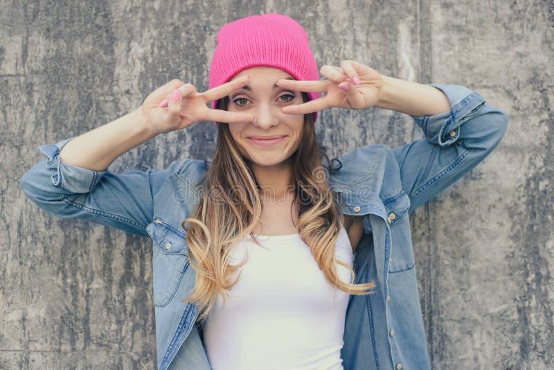 获得的妇女乐趣 有好心情,做鬼脸和显示v标志的妇女在她的眼睛附近 她在便衣和替换者打扮 库存图片
