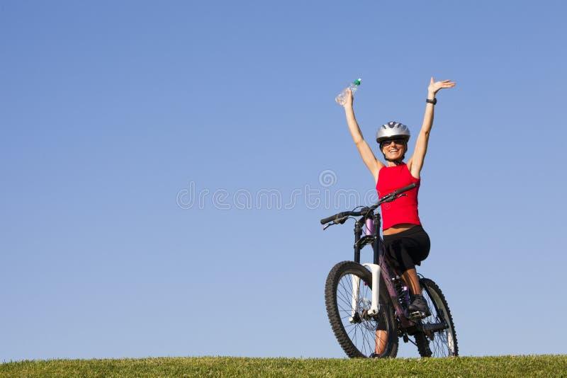 获得的妇女在自行车的乐趣 免版税库存照片