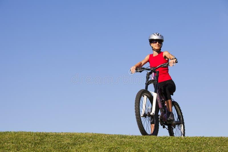 获得的妇女在自行车的乐趣 图库摄影