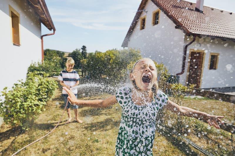获得的孩子与飞溅水的乐趣 图库摄影