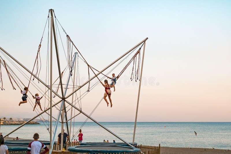 获得的孩子在跳跃在海滩的微型橡皮筋的乐趣 免版税库存照片
