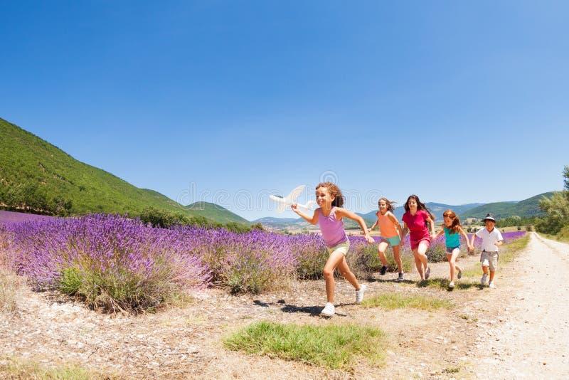 获得的孩子跑与玩具飞机的乐趣 库存照片