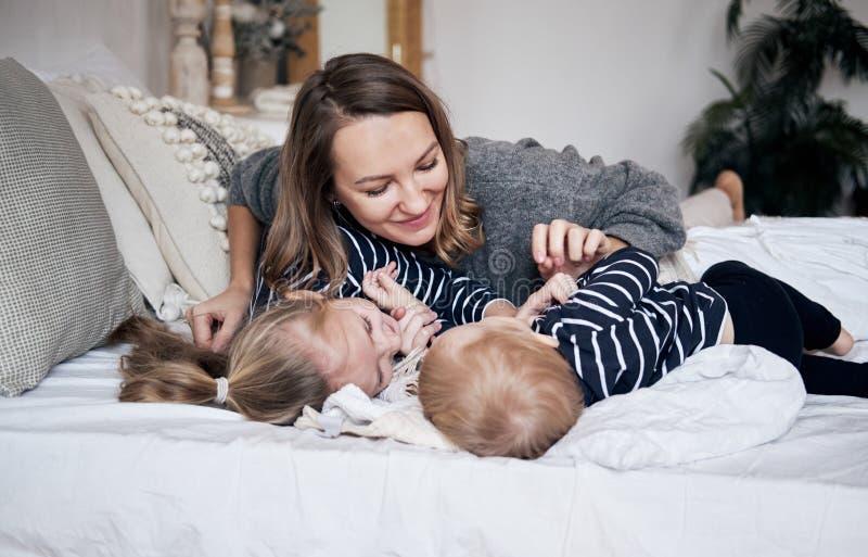 获得的家庭乐趣在家 使用与孩子的愉快的年轻母亲在卧室 拥抱在床上的兄弟和姐妹 晴朗的hol 免版税库存照片
