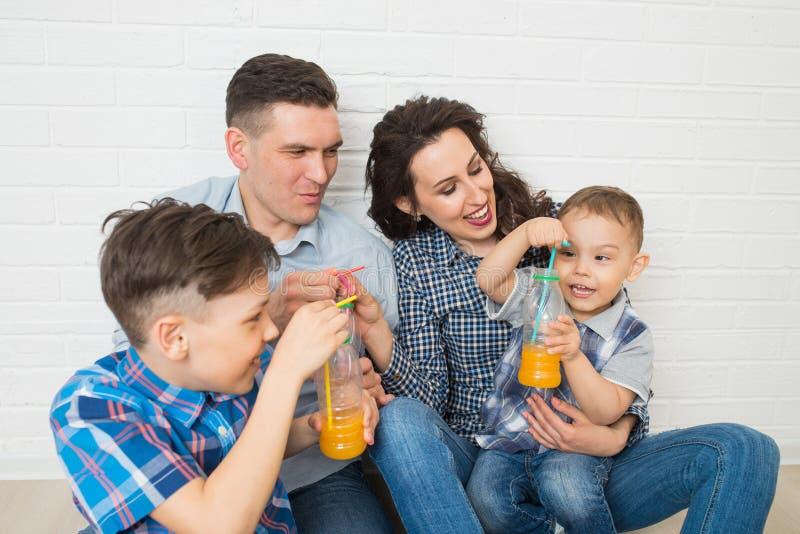 获得的家庭喝橙汁的乐趣使用秸杆 库存照片