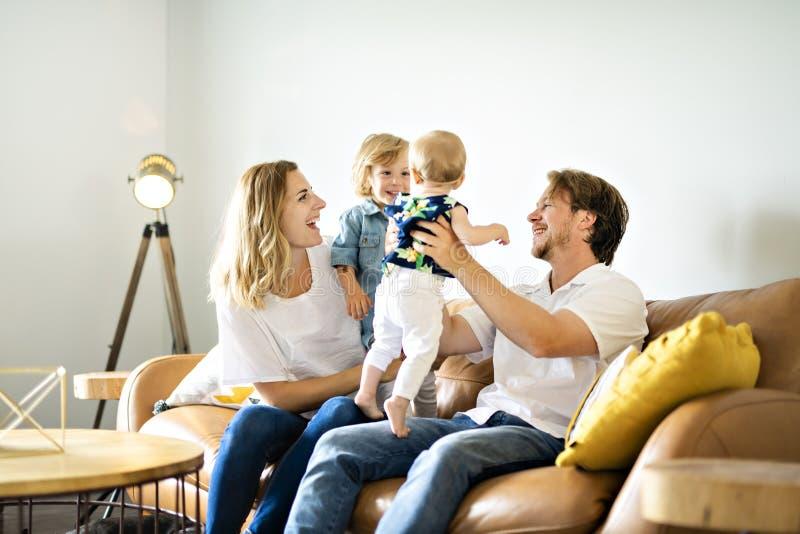 获得的家庭在沙发的乐趣 免版税库存照片
