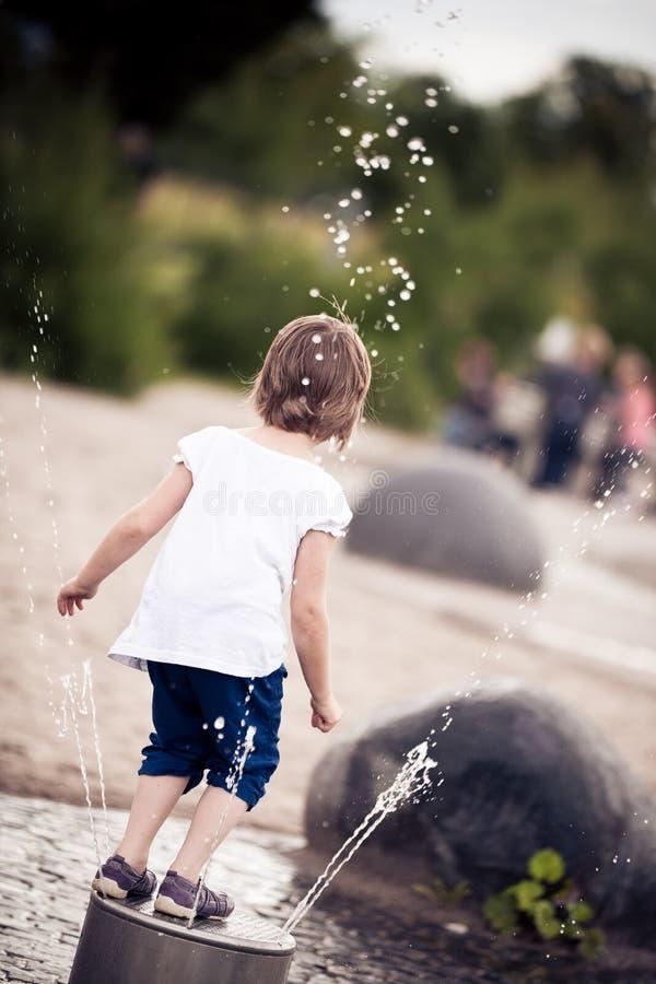 获得的小女孩在操场的乐趣 库存图片