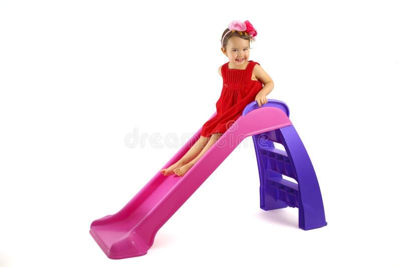获得的小女孩在被隔绝的幻灯片的乐趣 免版税库存照片