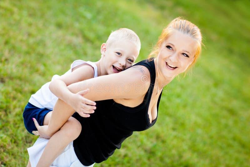 获得的小男孩与他的母亲的乐趣 免版税库存图片