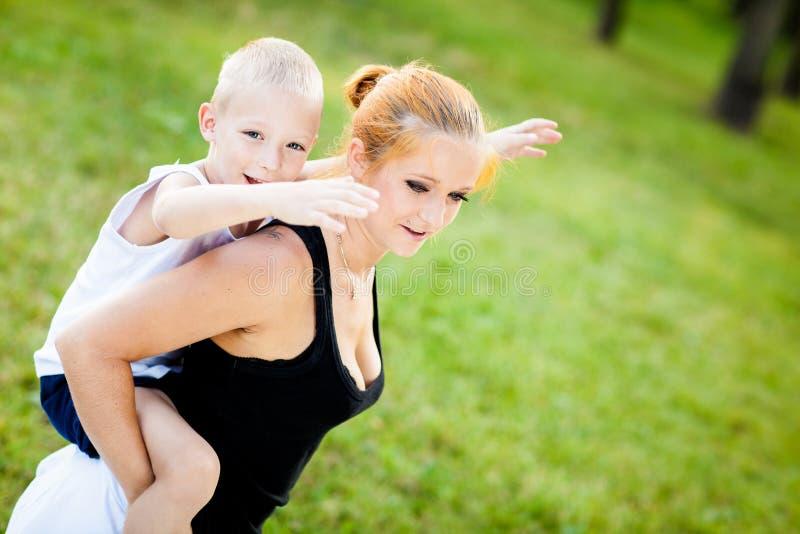 获得的小男孩与他的母亲的乐趣 库存照片