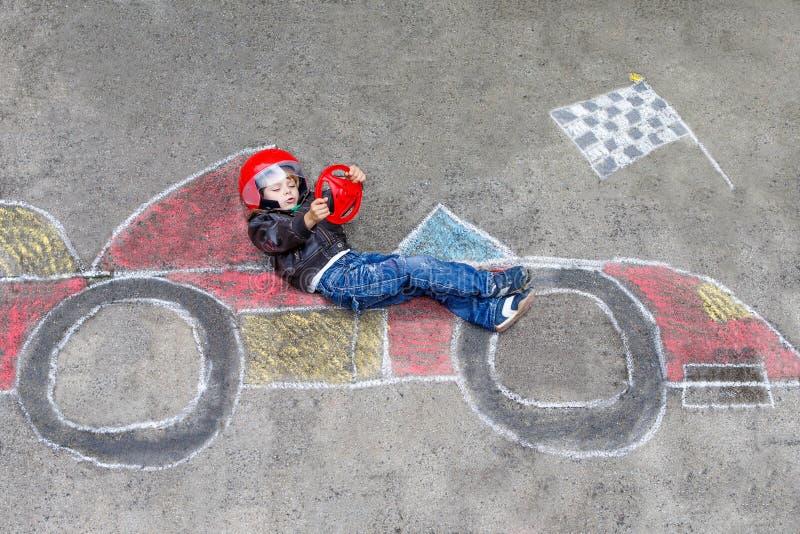 获得的小男孩与赛车图画的乐趣与白垩 库存照片
