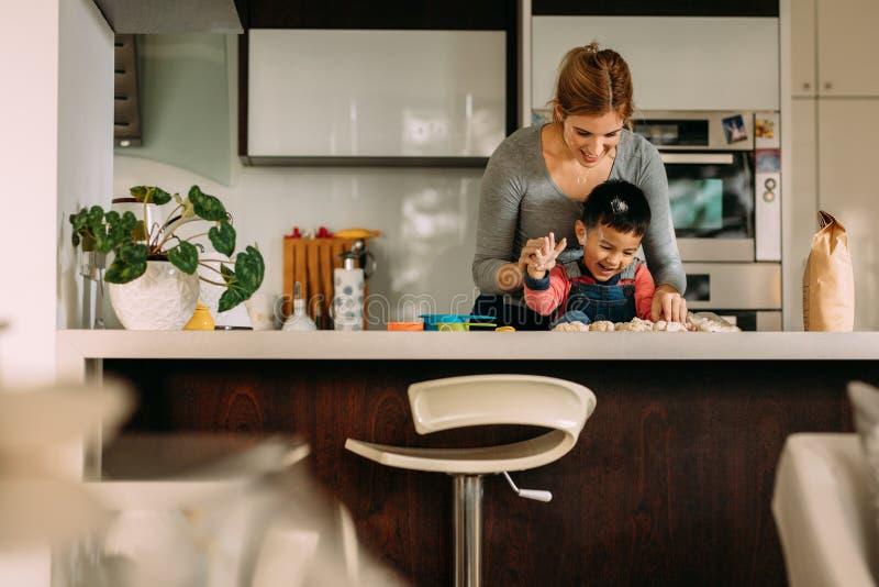 获得的小男孩做与母亲的乐趣曲奇饼 库存照片