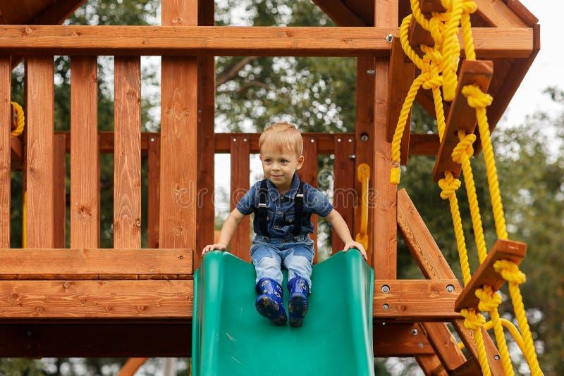 获得的小男孩在室外操场的乐趣 孩子的夏天活跃体育休闲 免版税库存照片