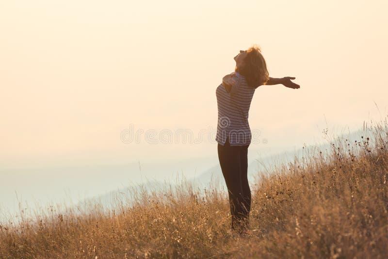 获得的少妇站立在山和在草地的乐趣 库存照片
