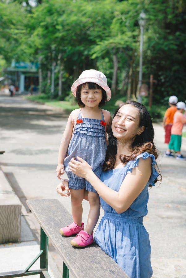 获得的幸福家庭与动物徒步旅行队公园的乐趣在温暖的夏日 库存图片