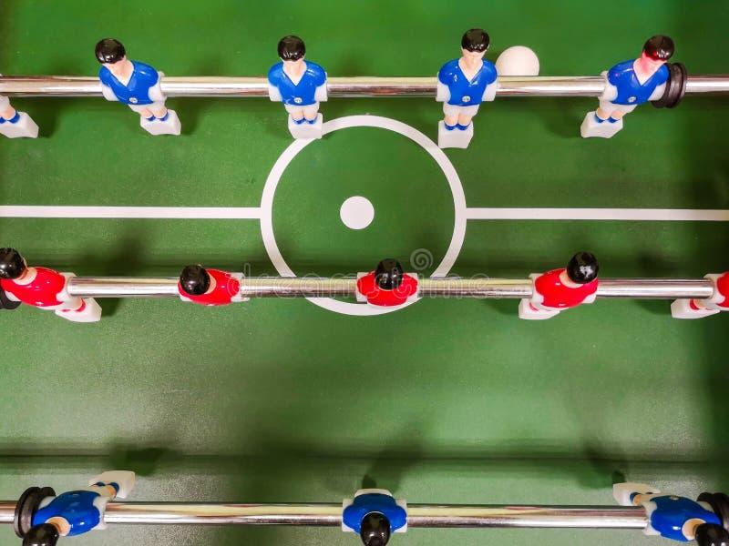 获得的朋友一起演奏foosball的乐趣 踢在断裂的同事桌橄榄球 享受桌足球的办公室人 免版税库存照片
