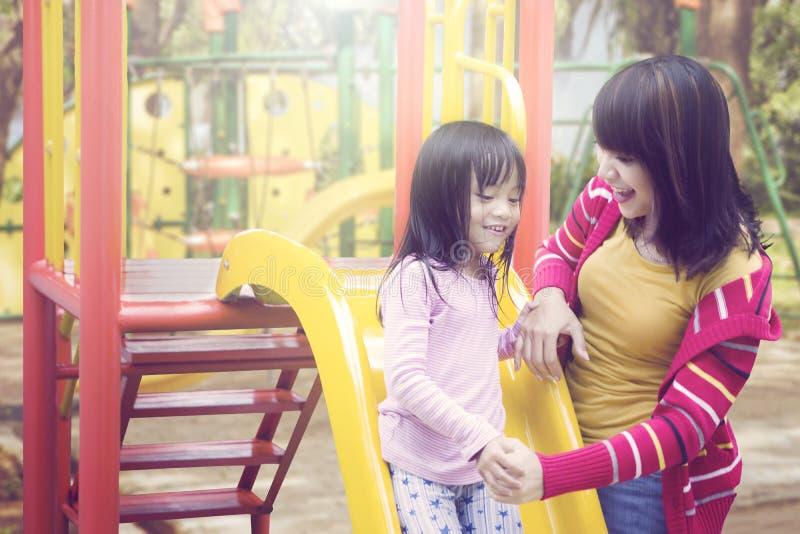 获得的母亲和的女儿与室外的幻灯片的乐趣 免版税库存照片