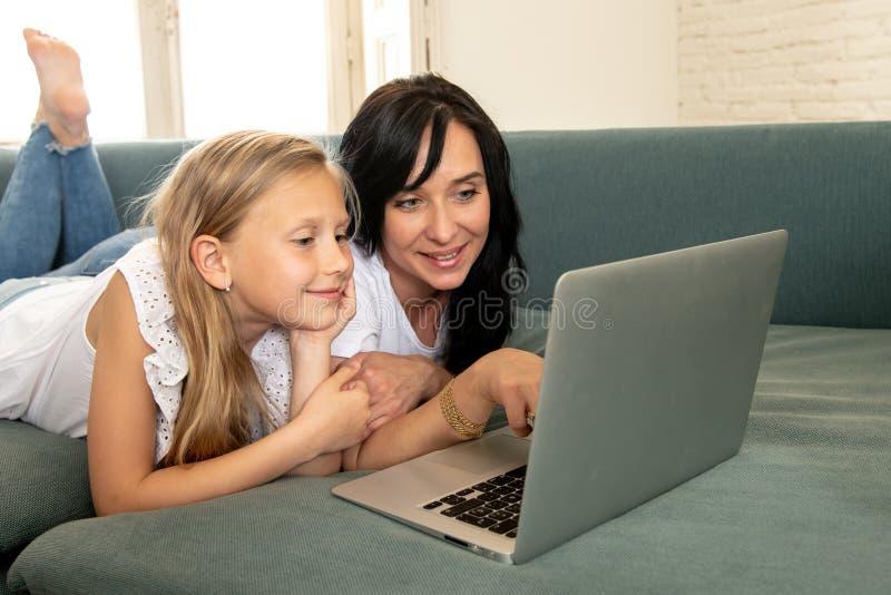 获得的母亲和的女儿微笑和一起使用和冲浪在膝上型计算机的互联网上的乐趣 库存图片