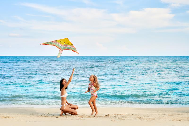 获得的母亲和的女儿飞行在热带海滩的乐趣一只风筝 免版税图库摄影