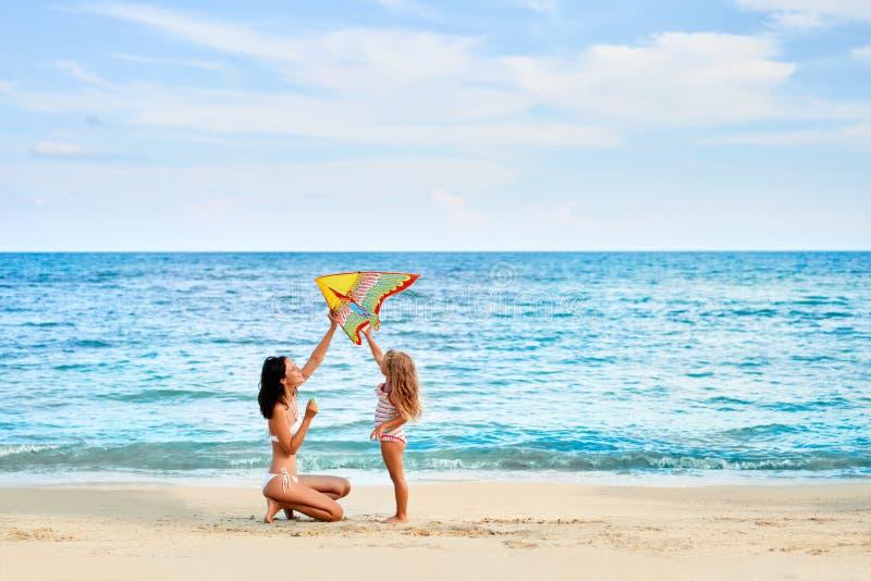获得的母亲和的女儿飞行在热带海滩的乐趣一只风筝 库存图片